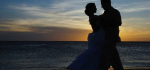 Romantic silhouette of wedding couple on the beach at sunset